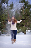 Beautiful girl in winter snow throws hands Royalty Free Stock Photography