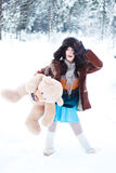 Beautiful girl on winter snowy forest background with teddy bear Stock Photo