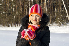 Beautiful girl in the winter of the sunset. Keeps the snow Stock Photos
