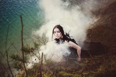 Beautiful girl witch conjures in the woods. Stock Photo