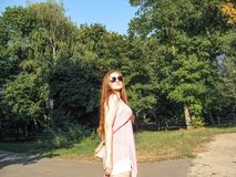 Beautiful Girl With Long Golden Hair In Sunglasses Looks At The Sun. Young Woman In Pink Clothes Walking In A Park On A Clear Royalty Free Stock Photography