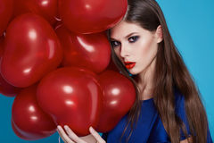 Beautiful girl wiwh red heart balloons evening makeup long hair Stock Photos