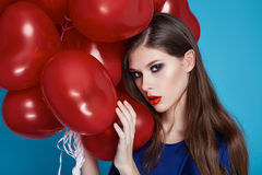 Beautiful girl wiwh red heart balloons evening makeup long hair Royalty Free Stock Image