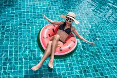 Beautiful girl Woman relaxing on watermelon lilo in pool. Blue water royalty free stock photo