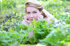 Beautiful girl in wood amongst green sheet Royalty Free Stock Images
