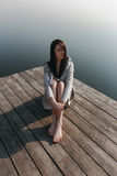 Beautiful girl on wooden pier near the water. In sunlight Stock Image