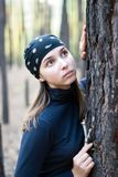 Beautiful girl in the woods. Dreaming beautiful girl with bandana in the woods leaning against the trunk of a pine tree Stock Photo