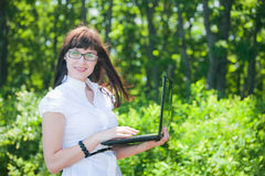 Beautiful girl in the woods with a laptop Royalty Free Stock Photos