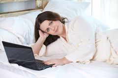 Beautiful girl. Work at home. Black notebook. White Bed Royalty Free Stock Images