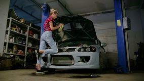 Backside view cute blonde girl in plaid red shirt and ripped jeans rubs the details under hood of the car in garage stock video