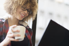 Beautiful girl working on her laptop while drinking coffee. Portrait of mixed race girl sitting by the window with her laptop Stock Photography