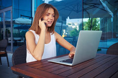 Beautiful girl working on laptop and speaking on the phone in su Stock Images