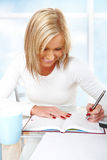 Beautiful girl working or studying. Taking notes Royalty Free Stock Photos