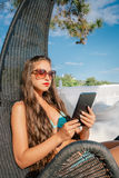 Beautiful girl working on the tablet at the beach Royalty Free Stock Image