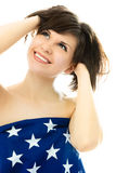 Beautiful girl wrapped into an American flag. Happy beautiful young woman wrapped into an American flag Stock Images