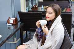 Beautiful girl wrapped in blanket holding a cup of tea Royalty Free Stock Image