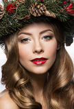Beautiful girl with a wreath of Christmas tree branches and cones. New Year image. Beauty face. Stock Photography