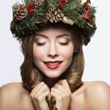 Beautiful girl with a wreath of Christmas tree branches and cones. New Year image. Beauty face. Stock Image