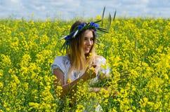 Beautiful girl in wreath of cornflowers on flowering rapeseed fi Stock Photo