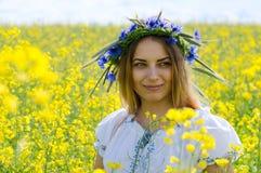 Beautiful girl in wreath of cornflowers on flowering rapeseed fi Stock Image
