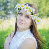 Beautiful girl with a wreath of daisies on her head Stock Photo