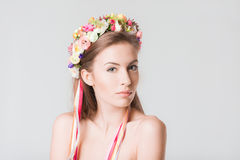 Beautiful girl with a wreath of flowers on head. Beautiful sexy young girl with a wreath of flowers on her head, with bare shoulders with beauty makeup, a cute Stock Image