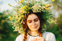 Beautiful girl in wreath of flowers  in meadow on sunny day. Portrait of Young beautiful woman wearing a wreath of wild flowers. Y Royalty Free Stock Photo