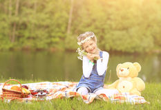 Beautiful girl in a wreath with a Teddy bear on a picnic Royalty Free Stock Photo