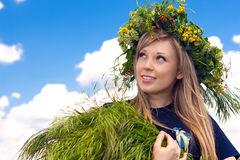 Beautiful girl in a wreath which reaps a crop in Royalty Free Stock Image