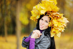 Beautiful girl with a wreath of yellow leaves on the head on a b Royalty Free Stock Photography