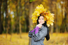 Beautiful girl with a wreath of yellow leaves on the head on a b Royalty Free Stock Photos
