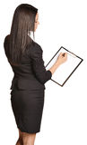 Beautiful girl writes a pen holder paper. Royalty Free Stock Image