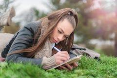 Beautiful girl writing in a book Stock Image