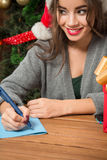 Beautiful girl writing New Year and Christmas congratulation. Close-up portrait of smiling beautiful girl holding a pen and thinking about nice New Year and Stock Images