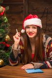 Beautiful girl writing New Year and Christmas congratulation. New Year and Christmas concepts. Portrait of beautiful girl sitting with a pen and writing a New Stock Photo