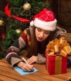 Beautiful girl writing New Year and Christmas congratulation. New Year and Christmas concepts. Beautiful girl writing New Year and Christmas congratulation while Stock Photo