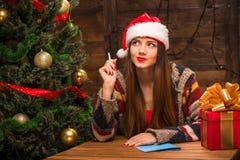 Beautiful girl writing New Year and Christmas congratulation. New Year and Christmas concepts. Beautiful girl thinking about New Year and Christmas Royalty Free Stock Photos