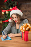 Beautiful girl writing New Year and Christmas congratulation. Happy smiling beautiful girl writing New Year and Christmas congratulation to her foreign friends Stock Photos