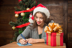 Beautiful girl writing New Year and Christmas congratulation. Beautiful lady writing New Year and Christmas congratulation to her relatives abroad while sitting Royalty Free Stock Photos