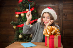 Beautiful girl writing New Year and Christmas congratulation. Portrait of beautiful girl sitting at the wooden table and thinking about interesting New Year and Stock Photo
