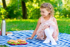 Beautiful girl 6 years old sitting on the plaid Royalty Free Stock Photography