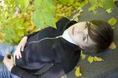 Beautiful girl among the yellow autumn leaves Royalty Free Stock Image