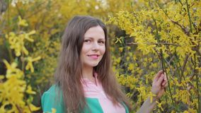 Beautiful girl among yellow blossom spring tree touching and smelling flowers slowmotion.  stock video footage