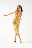 Beautiful girl in a yellow dress dancing. In white studio Royalty Free Stock Photos