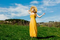 Beautiful girl in yellow dress and on mountain meadow with dandelions. royalty free stock photography