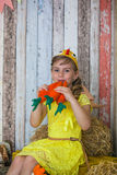 Beautiful girl in the yellow dress, playing with carrot Stock Photography