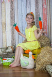 Beautiful girl in the yellow dress, playing with carrot Royalty Free Stock Photo