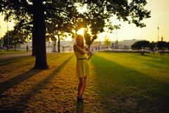 The beautiful girl in a yellow dress stand in beams of the sunset sun Stock Image