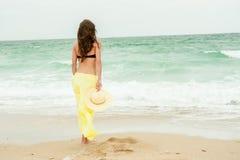 Beautiful girl in the yellow dress water beach Stock Photos