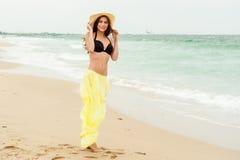 Beautiful girl in the yellow dress water beach Royalty Free Stock Photo